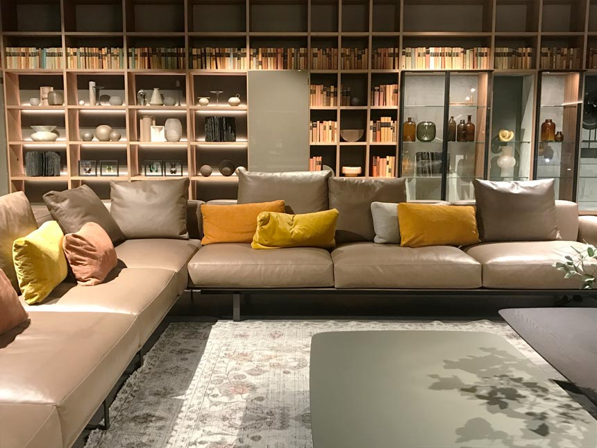 A living space installation with a large bookcase and two sectional leather sofas in a contemporary setting.