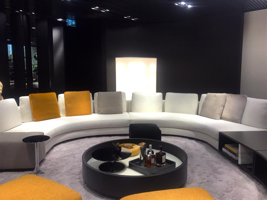 A big contemporary sitting lounge in a circular arrangement with a round black coffee table in the middle. Everything has a vibe from the 70's. As seen at Minotti.