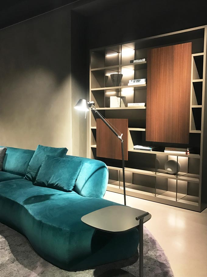 A teal velvet sofa in a contemporary setting in front of a dark stained wooden bookcase from Molteni at the imm Cologne 2020.