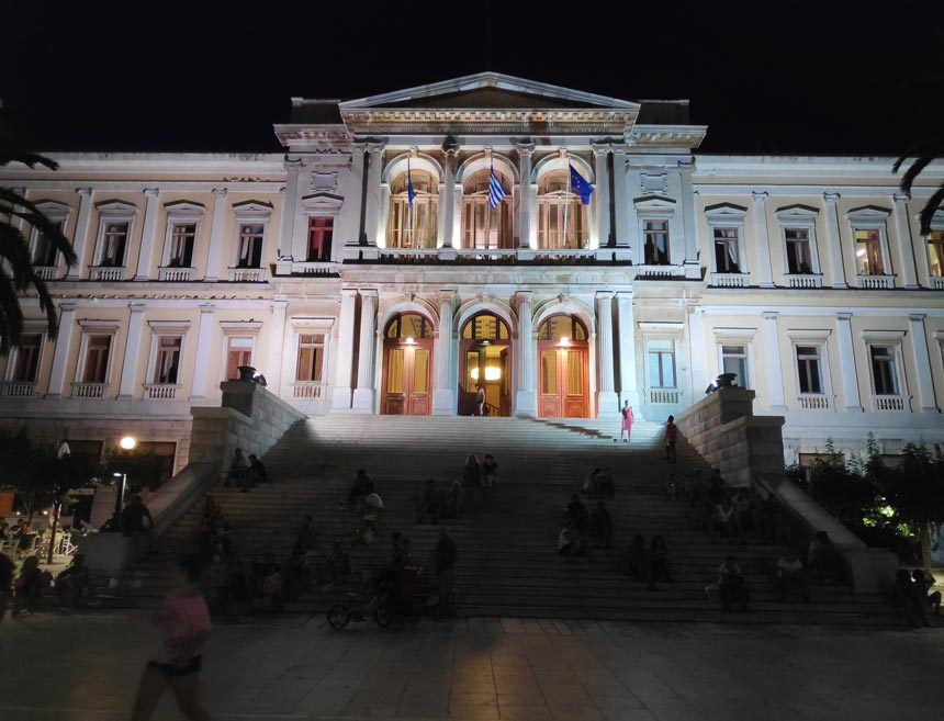 The Town Hall of Hermoupolis in Syros at night, pictured with a smartphone.