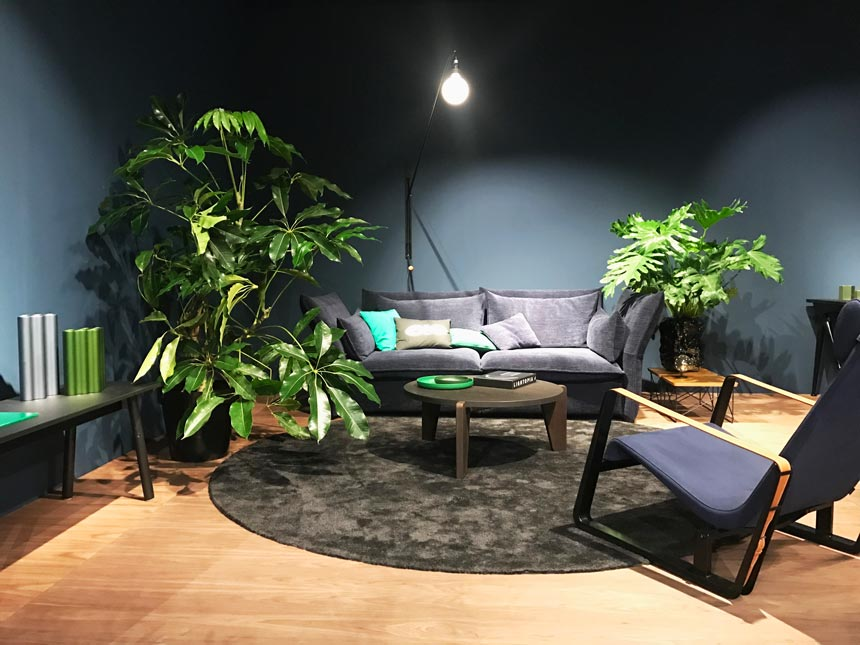 A dark grey contemporary sitting lounge by Vitra that includes a sofa, an armchair and some big plants.