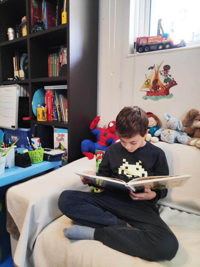 Tips for encouraging kids reading: A boy sitting on a sofa besides a bookcase reading a book. Image by Velvet.