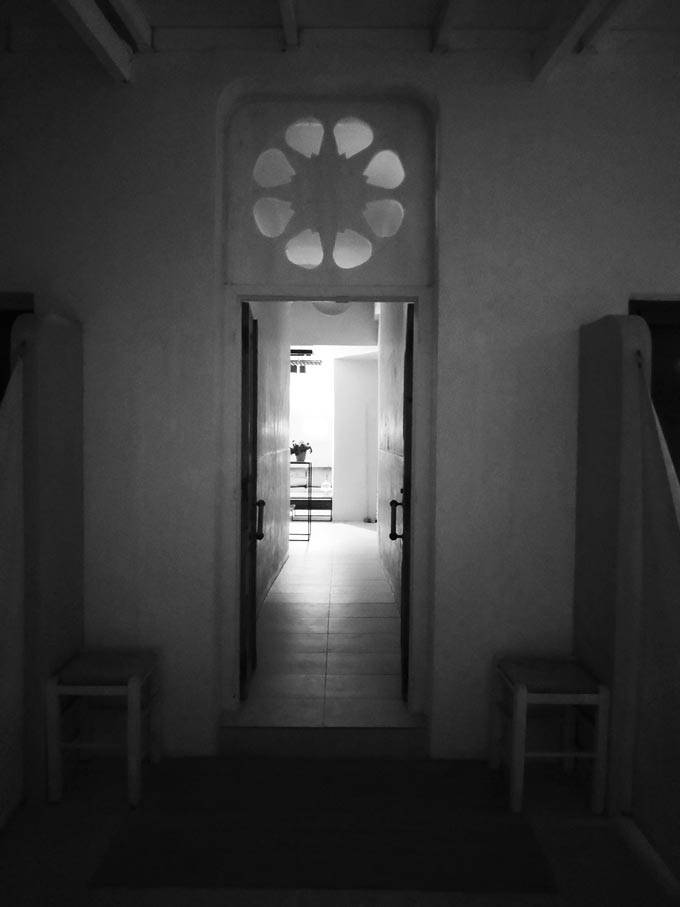 A black and white image of an open entry door lending views to a corridor and a room inside.