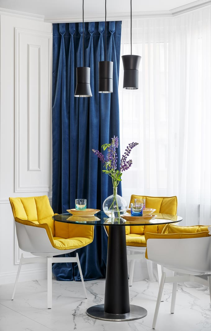 A closer view of the everyday dining set situated by a bright bay window, featuring classic blue drapes over shear white curtains and yellow upholstered armchairs. A bold combo in this luxurious apartment in Moscow. Image: Covet House/Sergey Krasyuk.