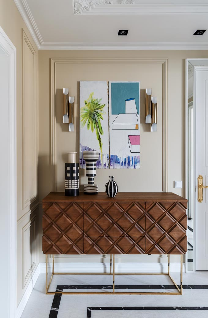 View of the entry-table at the hallway of a luxurious apartment in Moscow featuring a patterned wooden sideboard with brass details. Image: Covet House/Sergey Krasyuk.