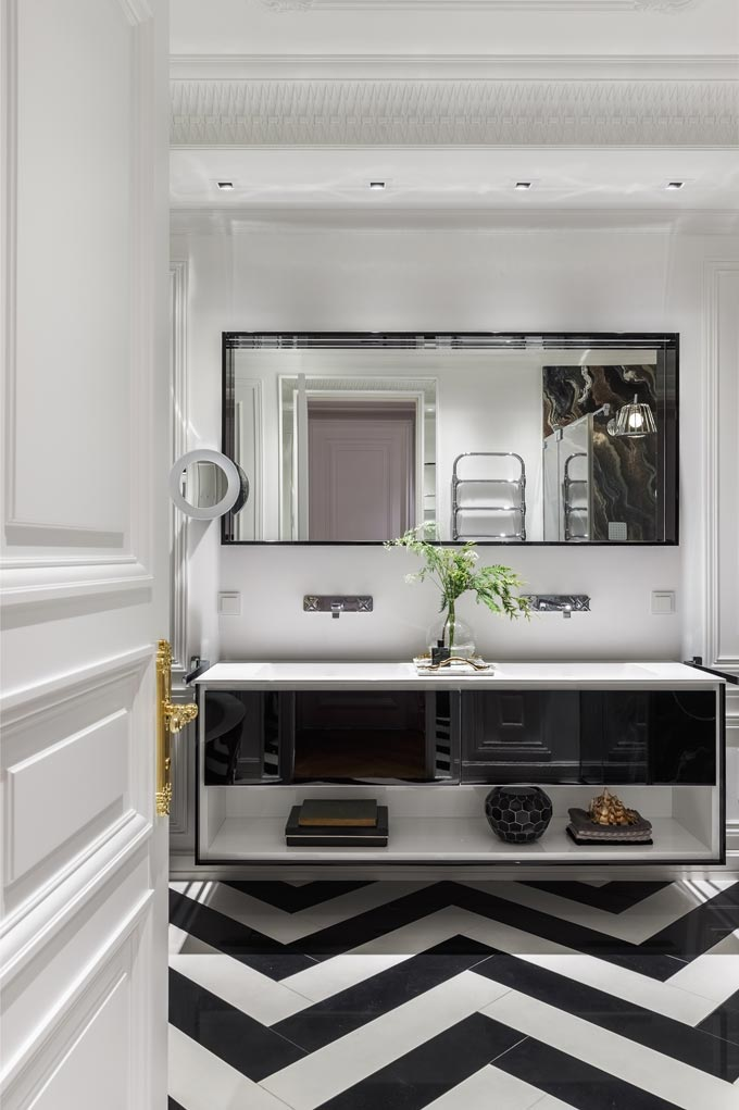 View of the master bathroom as you walk in with a distinct black and white herringbone pattern floor in this luxurious apartment in Moscow. Image: Covet House/Sergey Krasyuk.