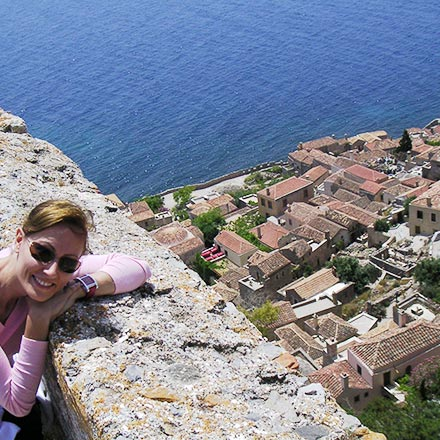 Velvet, the author, by the wall of a Medieval fortress in Monemvasia. In the background, the castle town of Monemvasia and the Aegean Sea.