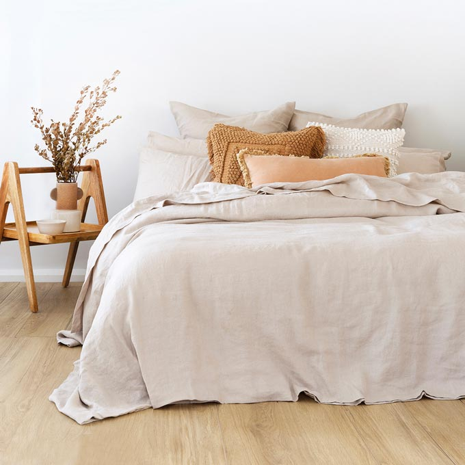A stylish Scandinavian chic bright bedroom with an eye-catching nightstand and beautiful linen bedding. Photo: Bambury..