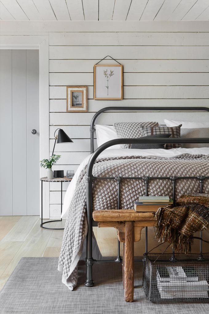 A Country chic styled bedroom with a round bedside table next to the steel frame bed. Image by Amara.