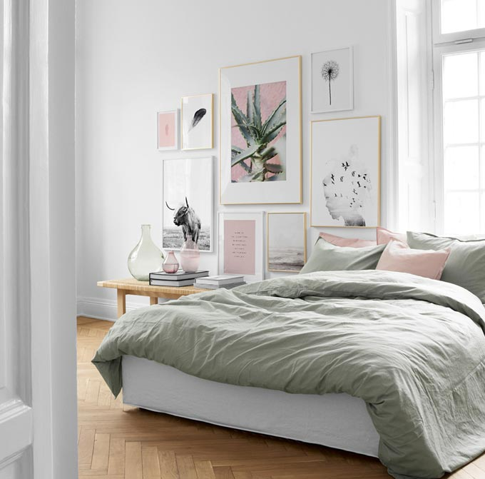 A contemporary bright white bedroom with soft sage and pink accents, a bench for a bedside table and a gorgeous art gallery wall. Image: Desenio.