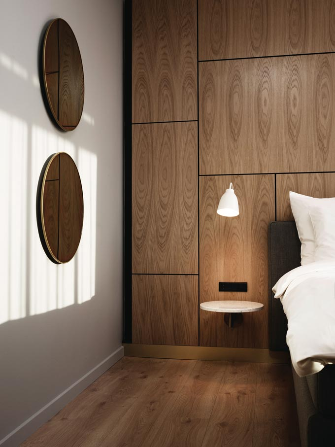 The Fritz Hansen Caravaggio Read Wall Light standing out against the wooden wall paneling, casting light upon a small white shelf that serves as a nightstand. Very sophisticated. Image: Nest.co.uk.