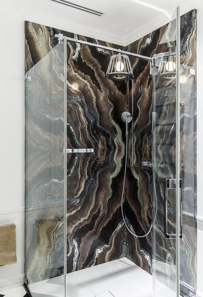 View of the shower cubicle with an impressive dark colored and veined marble accent wall. This bathroom belongs to a luxurious award winning apartment in Moscow. Image: Covet House/Sergey Krasyuk.