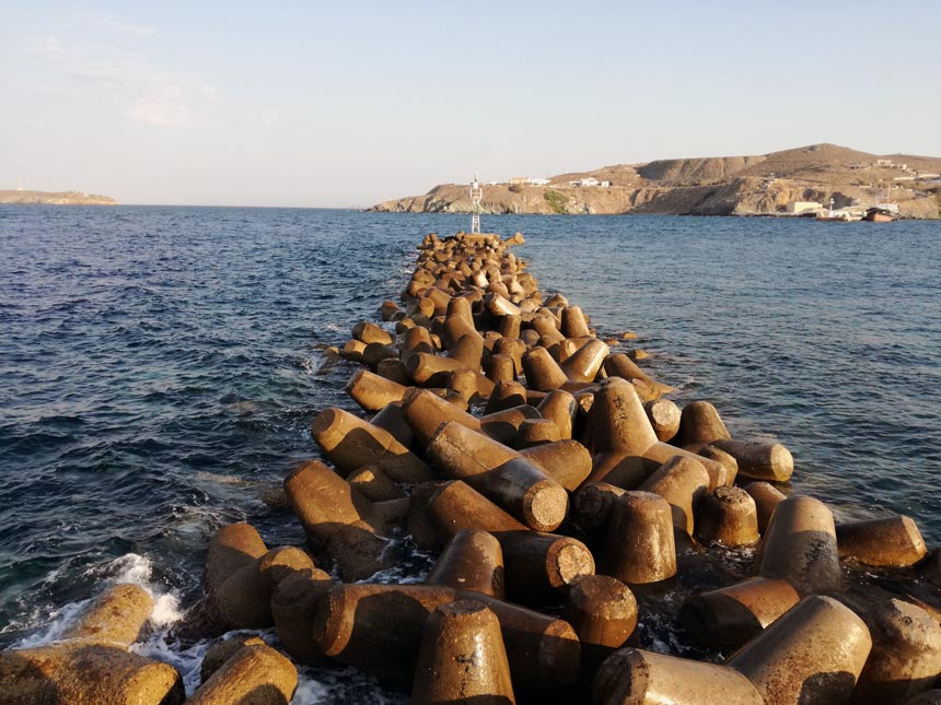 Wave breaking boulders aligned by the port of Hermoupolis, in Syros. A smartphone image.