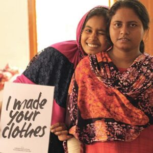 Two young women from India holding up a sign that reads 'I made your clothes.' Image: Secret Projects.