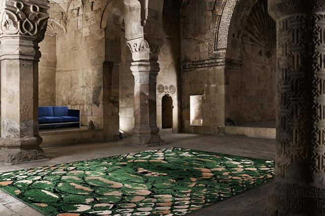 Interior Trends 2020. Jaw dropping rug! The green reptile pattern rug lays in the middle of an old monument with a blue sofa in between a wall recess. The neo-heritage trend is one of design trend that is on the rise for 2020.Image via Rug'Society.