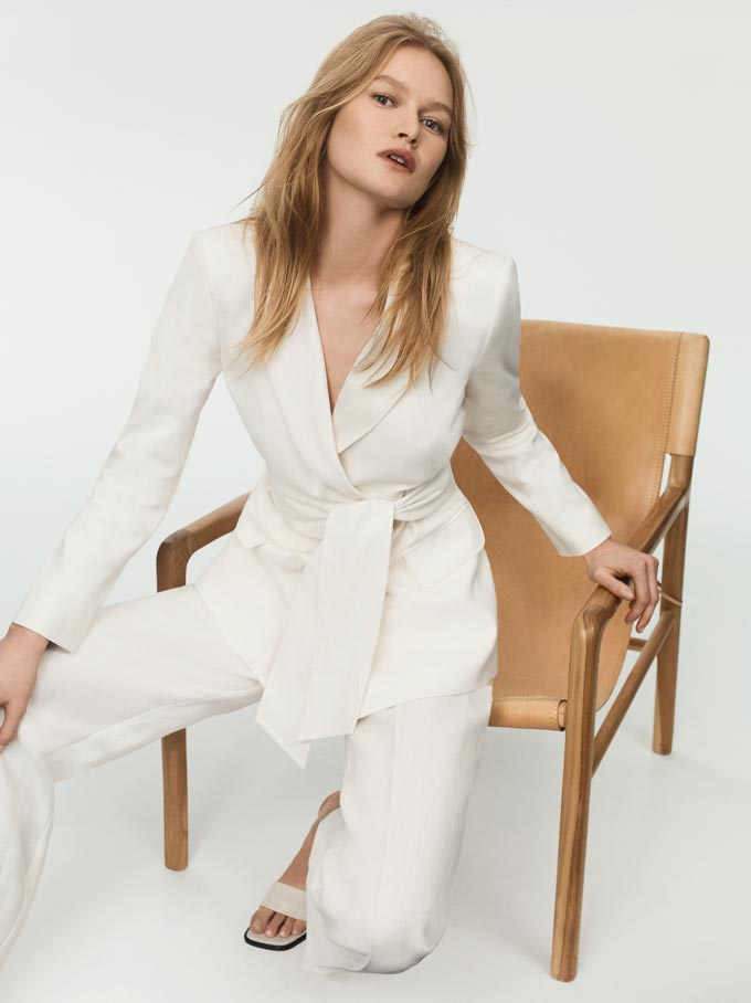 A woman sitting on a camel chair, wearing an all white power suit. Image: SABA.