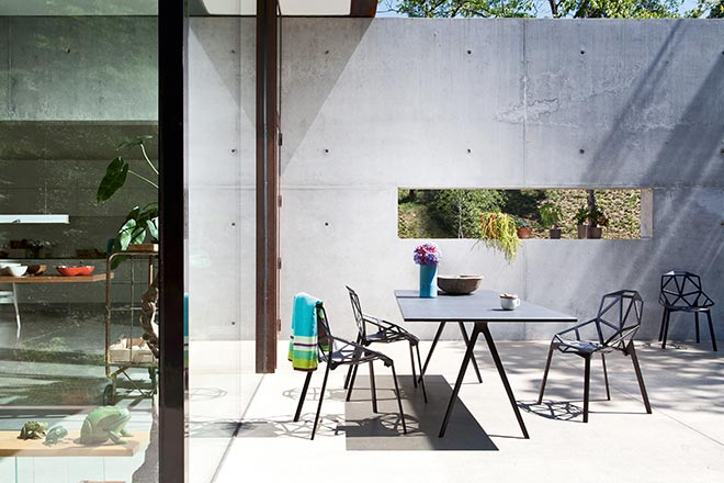An outdoor contemporary minimal setting becomes so much more interesting with the geometry of a Maggis black chair designed by Konstantin Grcic. Image by Nest.co.uk.