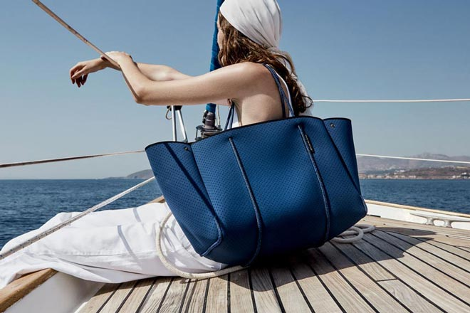 A woman on board a sailing boat carrying a large classic blue tote bag sitting on the deck and gazing at the sea. Image via State of Escape. Pantone's classic blue.