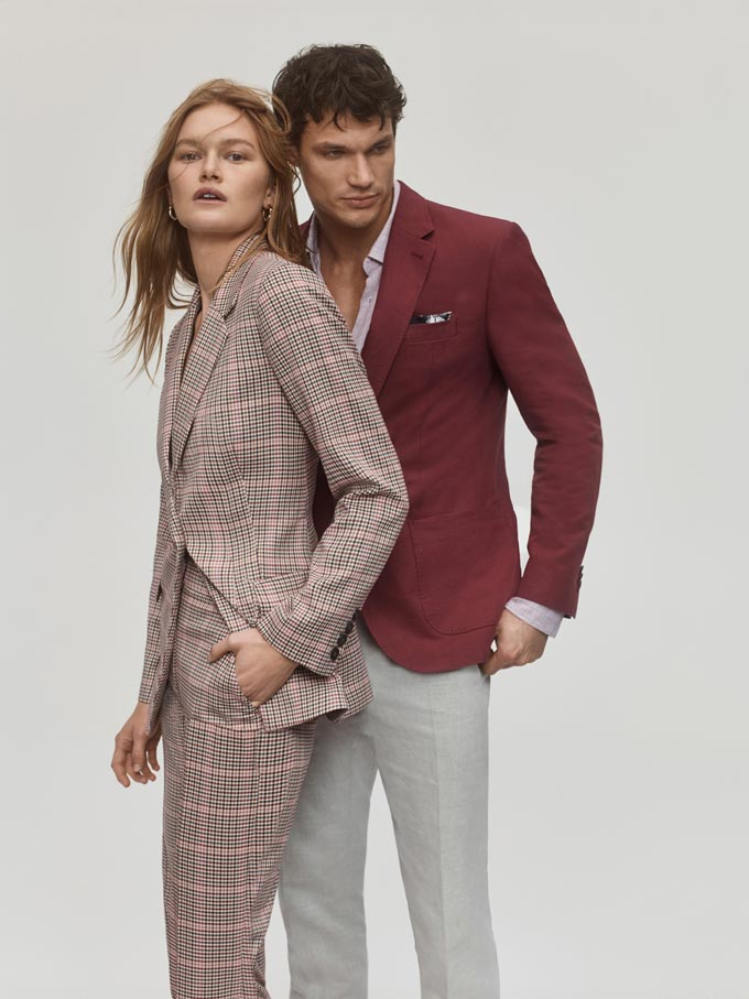 A couple. Woman in a check suit and man in light grey pants paired with a muted burgundy suit jacket. Image: SABA.