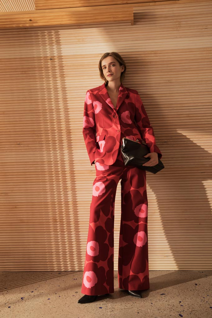 A stylish woman dressed in a bold red suite with an oversized flower print. Image: Marimekko.