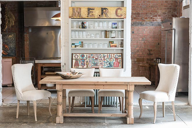 What a beautiful dining space - a fusion of industrial style with inox details and exposed brick wall accents and rustic elements due to this fab looking dining table combined with white dining chairs. Image by Houseology.