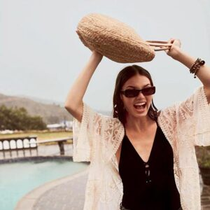 A woman in a black one piece suit wearing golden hoop earrings and holding a straw bag over her head as she's walking by a pool. Image: Accessorize.