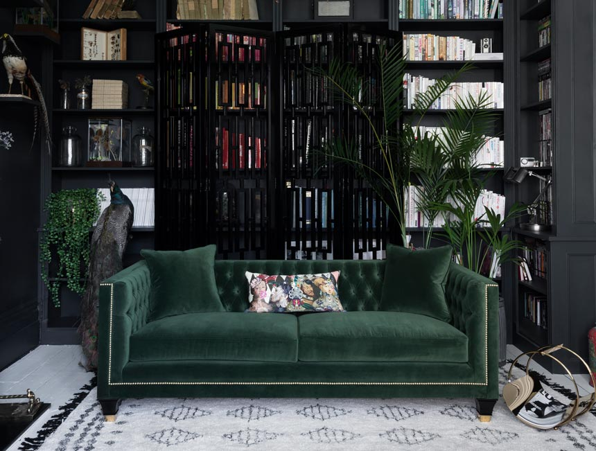 A stunning green velvet sofa from the Balfour designer sofa collection in front of a black screen and a wall to wall black bookcase. Image: Sweetpea & Willow.