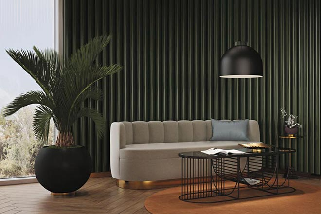Decorating with intention: The AYTM Luceo round pendant light hanging over a sofa with a fluted back. A wired frame coffee table and a large plant pot fill in the setting against a dark fir green textured wall. Image via Nest.co.uk.