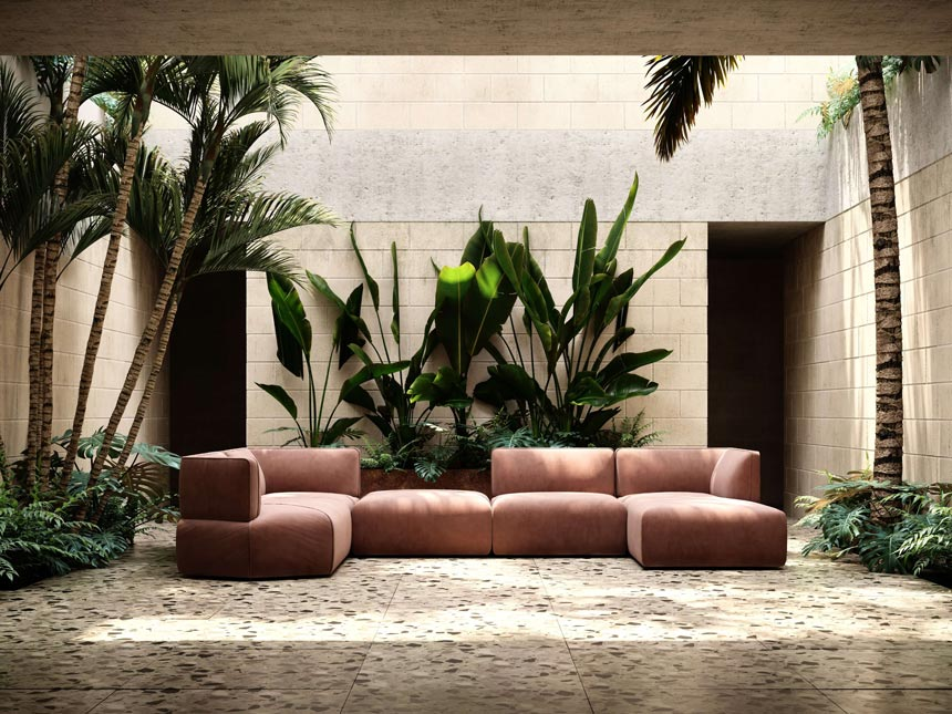 A modular contemporary sofa in a blushed pink velvet fabric resting on terrazzo tiles with lots of big green plants on the side and at the background. Image: Domkapa.