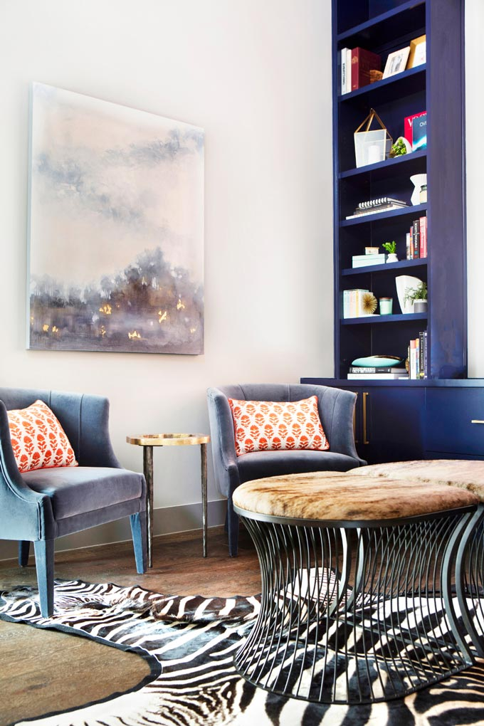 A study room furnished with two light blue velvet armchairs, blue built in bookcases and a zebra cowhide on the floor. Image: Brabbu Design Forces.