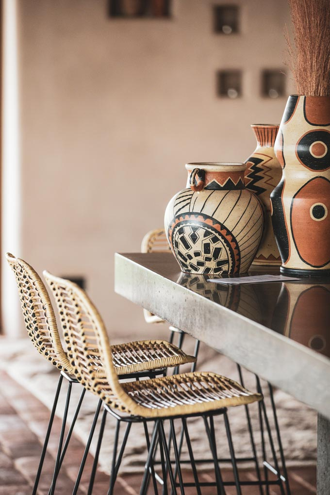 Ceramics with patterns in earth tones is another brilliant way to decorate. A summery setup with rattan dining chairs and ceramic vases on a grey dining table. Image: OZ Design Furniture.