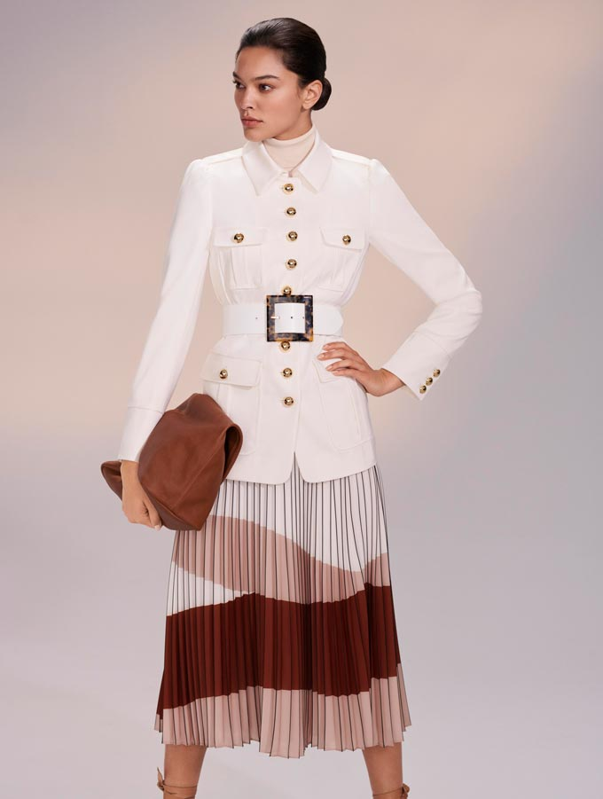 Transitional winter to spring outfits. A chic woman dressed in a white utilitarian jacket paired with a color blocked skirt in earthy tones. Image: Hobbs.