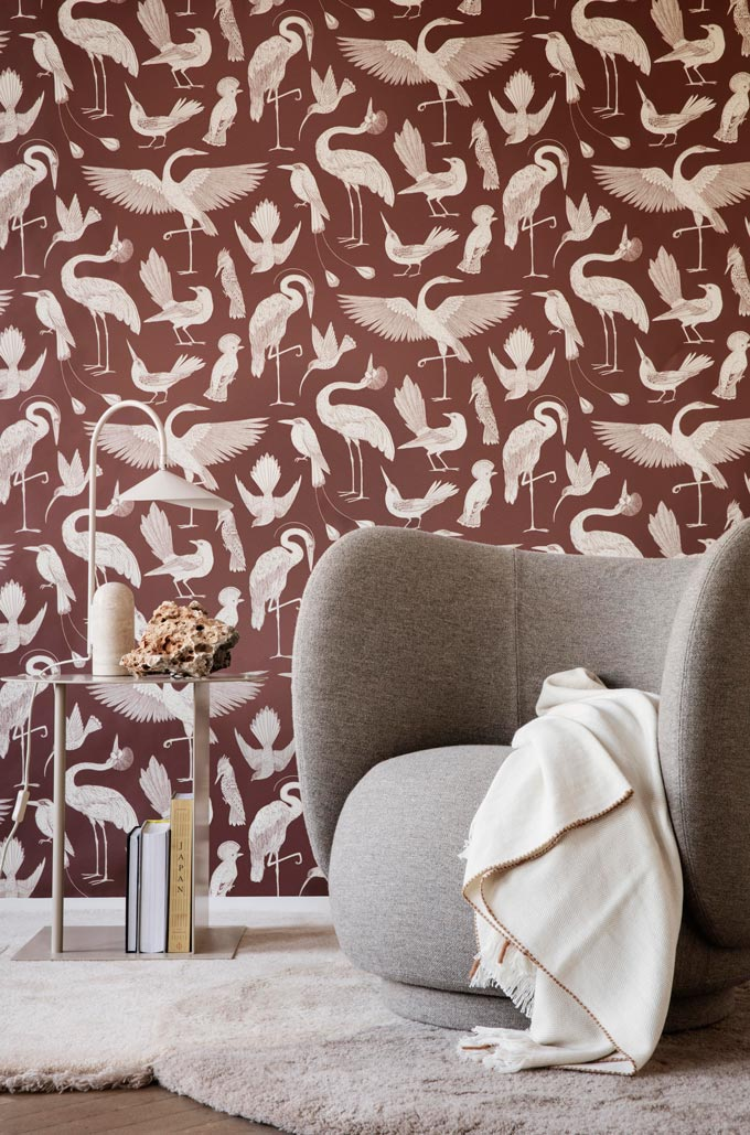 A fab looking light grey armchair in front of a pattern brown wallpapered wall. Image: Nest.co.uk.