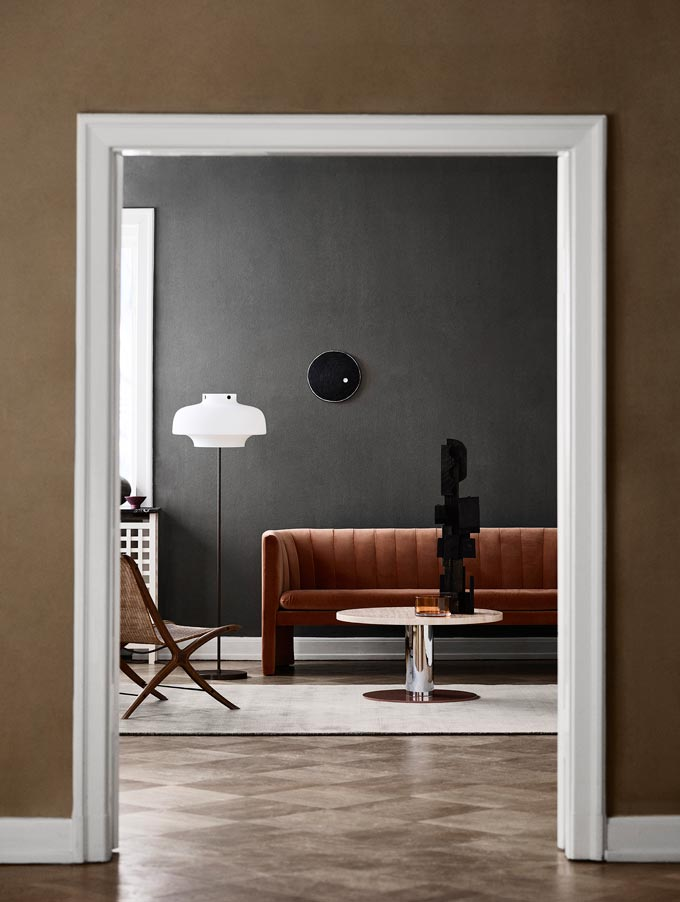 Peeping through a doorway into a contemporary minimal living room with earth tones. Image: Nest.co.uk.