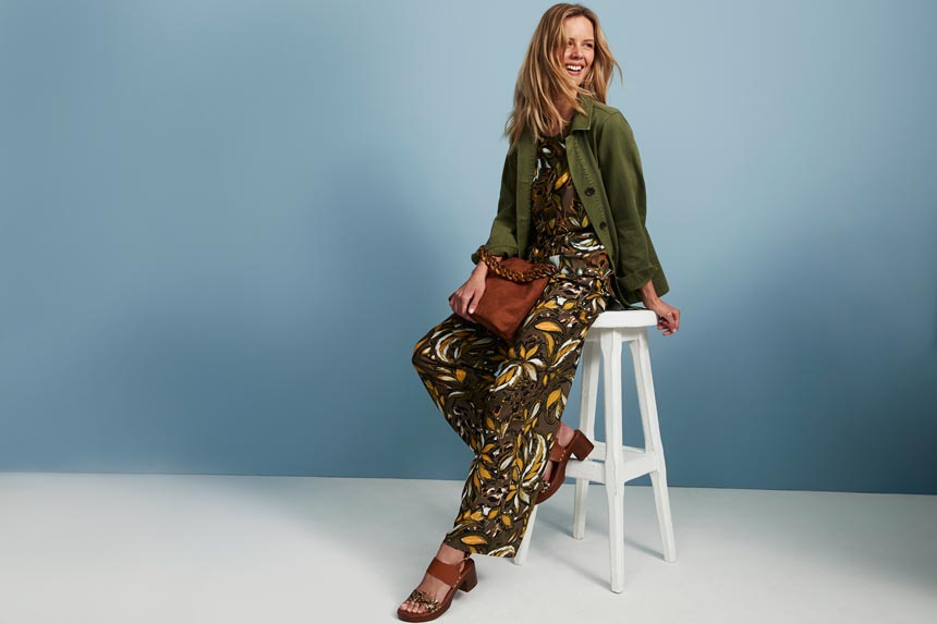 A khaki jumpsuit with a big flower print paired with a tan leather bag and sandals and a khaki jacket. Image: Matalan.