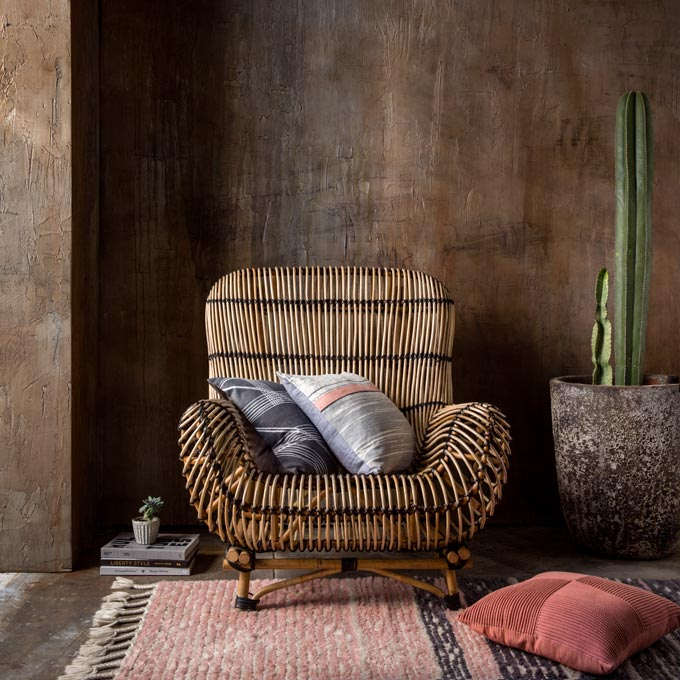 An earth toned wall acting as the backdrop to a rattan armchair. Image: KAS Australia
