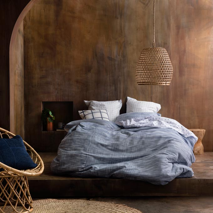 A stunning bedroom with brown walls and a bed with blue linens. A fantastic combo. Image: KAS Australia.