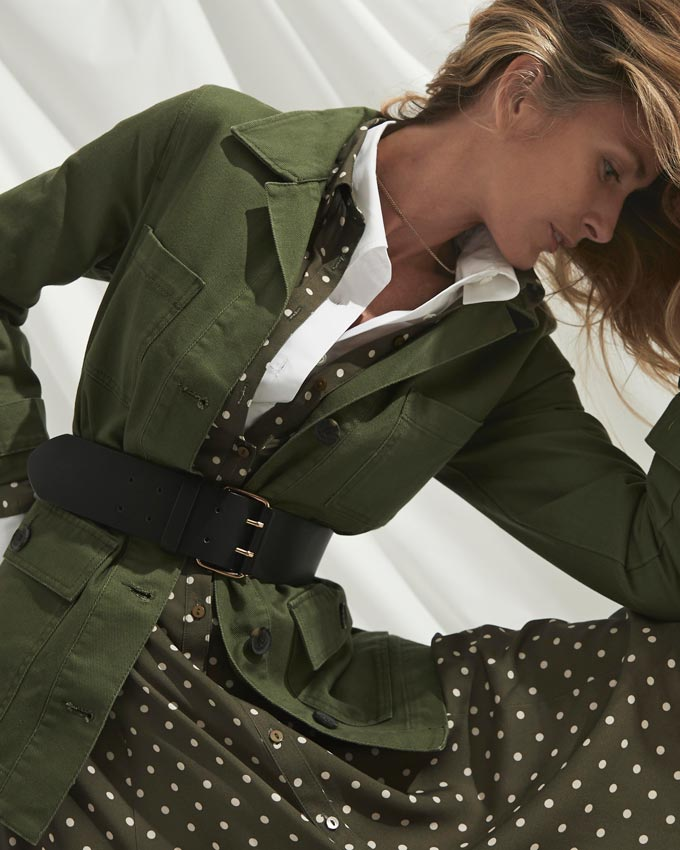 A khaki polka dot dress paired with a white shirt under and a khaki utilitarian jacket. Image: Matalan.