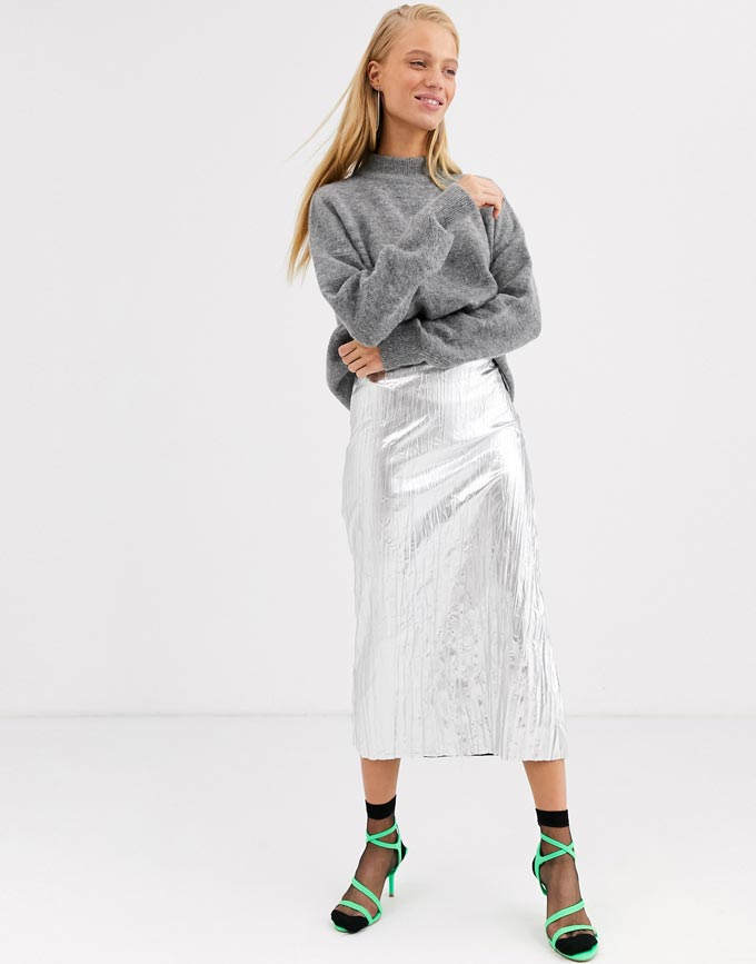 A woman wearing a grey sweater, a silver midi skirt, shear black ankle socks and neon green high heel sandals. Image: ASOS. A transitional winter to spring outfit idea.