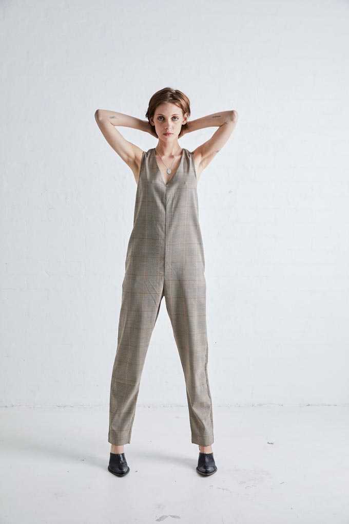 A jumpsuit with a plaid pattern paired with black mules. Image: NEUW Denim.