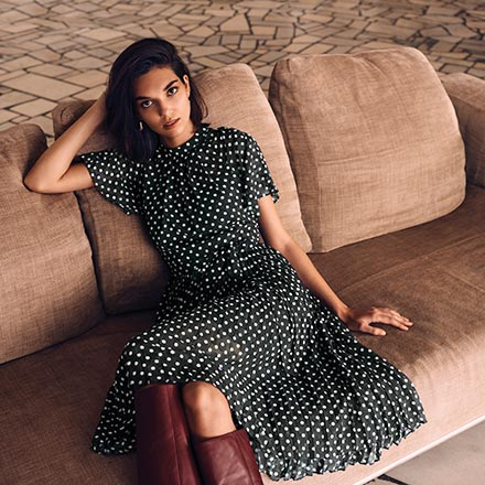 Midi navy blue polka dot dress with pleats paired with camel knee high boots. Image: SABA.