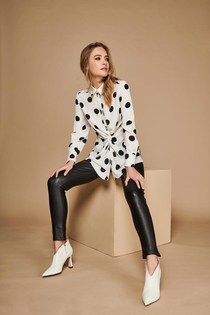 A chic transitional winter to spring outfit with a white polka dot top, black leather leggings and white booties. Image: M&Co.