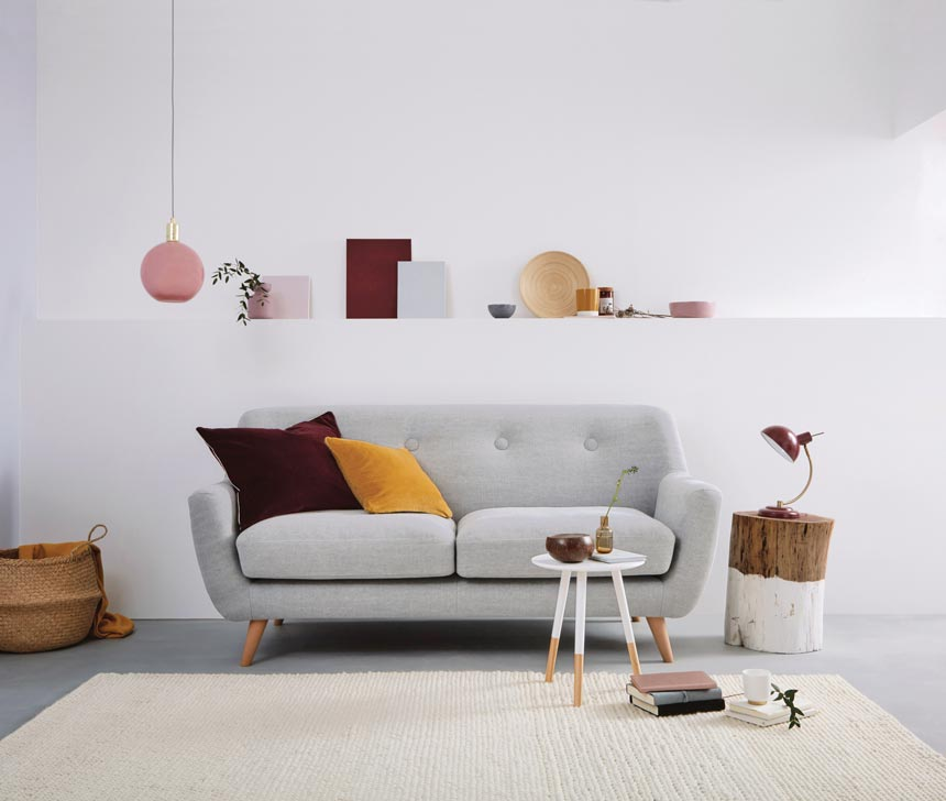 A light grey sofa of wool with two velvet throw pillows in burgundy and mustard for that pop of color in this minimal contemporary setting. Image: Dfs.