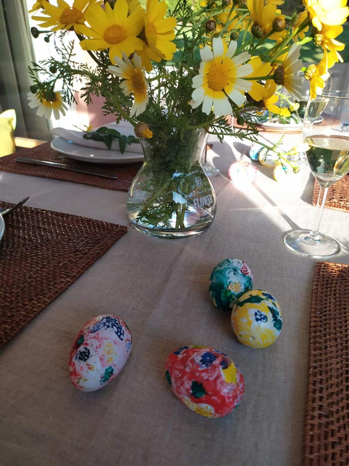Hand painted eggs and a vase with yellow daisies on a dining table.