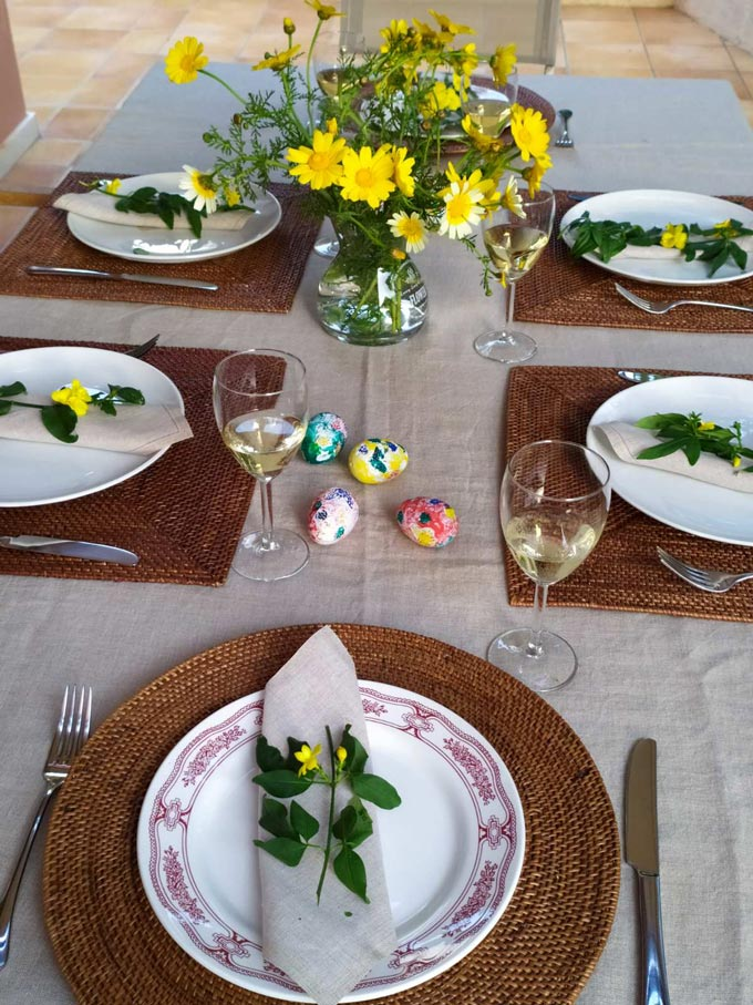 View of an Easter table setting with yellow daisies as a centerpiece.
