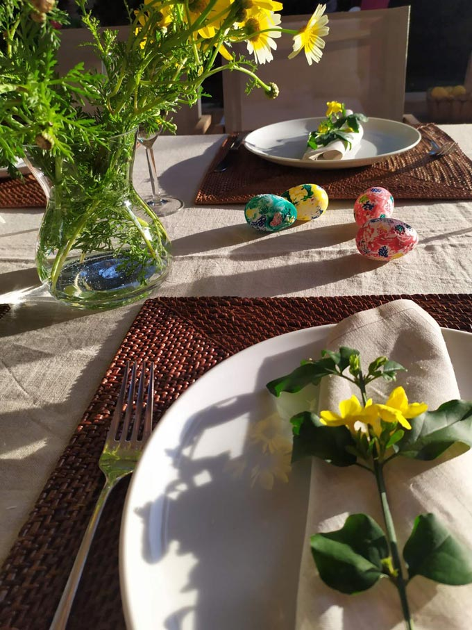Detail view of an Easter table setting with yellow wildflowers.