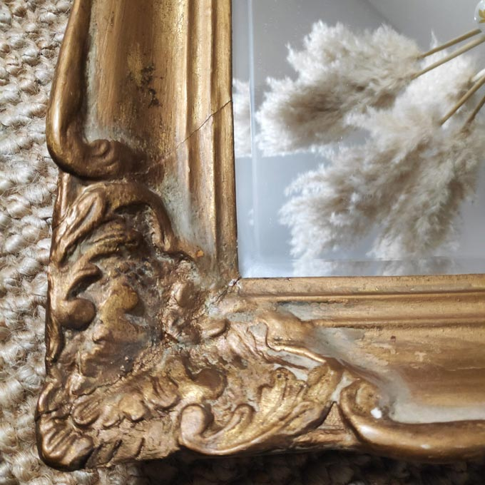 Detail view of a vintage gold gilded mirror with the reflection of Pampas grass.